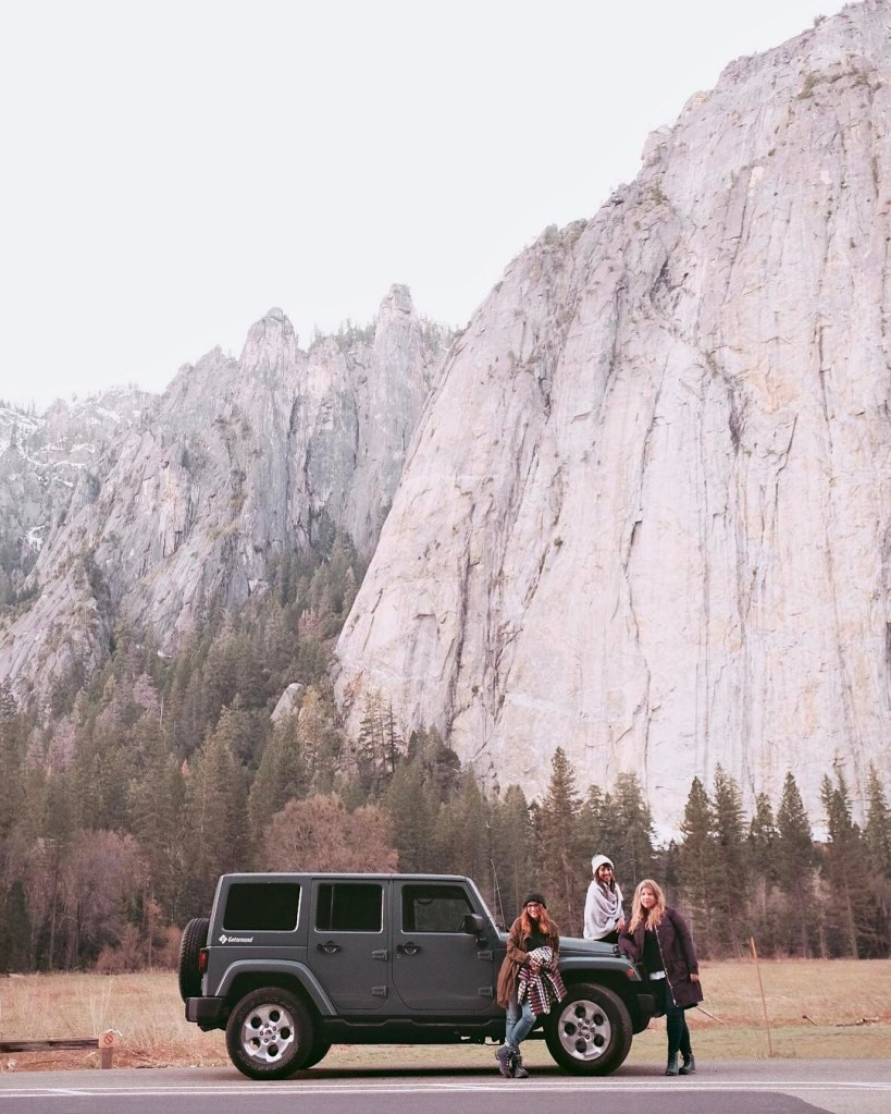Three girls standing next to and sitting on a Jeep car in Yosemite National Park.