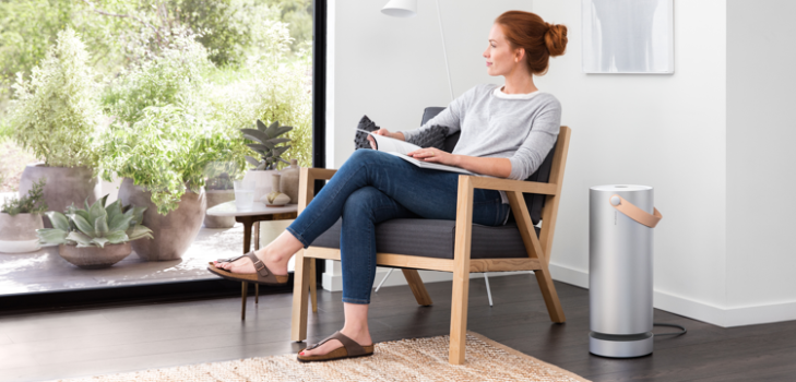 Woman sitting down reading magazine enjoying the fresh air from her Molekule air purifier
